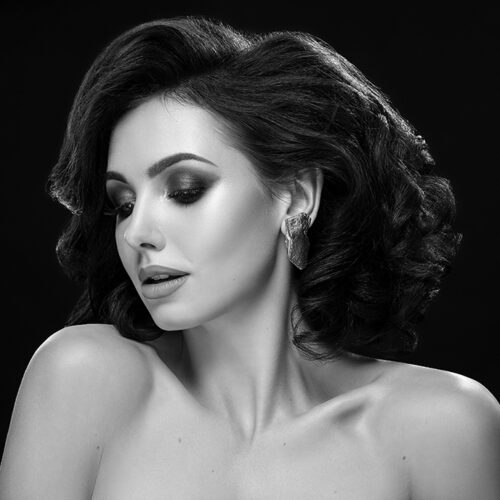 Black and white portrait of beautiful, charming and elegant woman looking down. Charming and lovely model with naked shoulders, perfect skin and volumed, wavy hair posing.